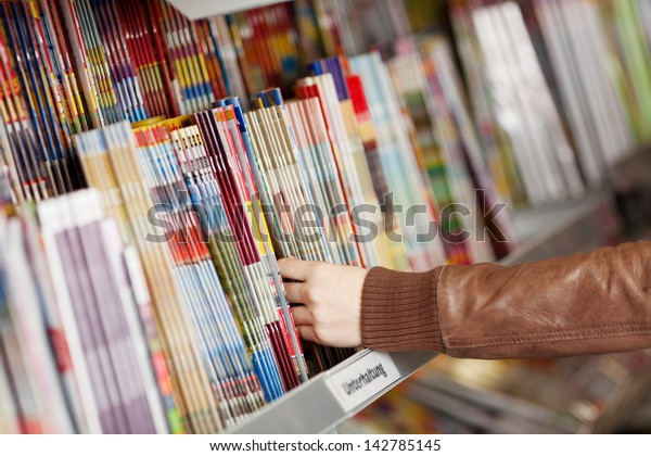 Closeup of woman's hands choosing magazines from shelf in supermarket