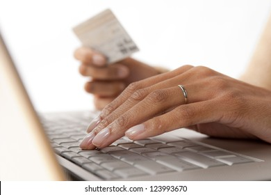 Close-up of woman's hands holding a credit card at a computer keyboard