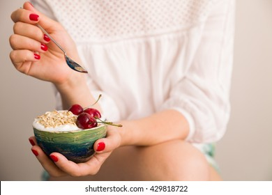Closeup of woman's hands holding a cup with organic yogurt with oats and cherries.  Breakfast or snack. Healthy eating and lifestyle concept.