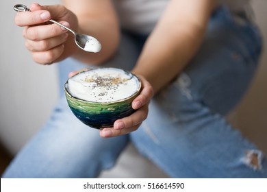 Closeup of woman's hands holding cup with organic yogurt with blueberries, coconut and fresh mint. Homemade vanilla yogurt in girl's hands. Breakfast, snack. Healthy eating and lifestyle concept
