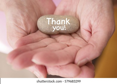 closeup of womans hands holding a stone with the words thank you written on it