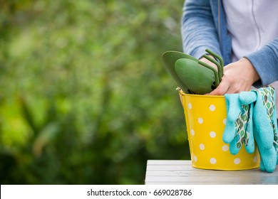 closeup of woman's hands holding yellow metal bucket with rubber gloves and garden tools on nature background. Girl in the garden.