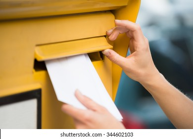 Closeup of woman's hands inserting letter in mailbox