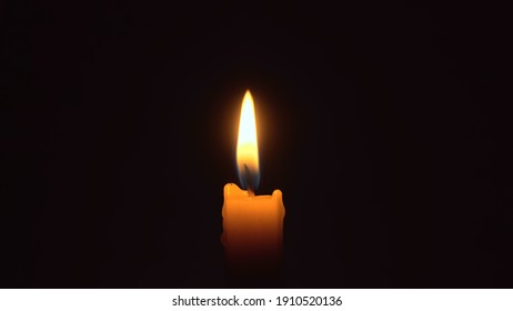Close-up of a woman's hands lighting a candle with a match in the dark, it burns and after a while a gust of wind extinguishes it.