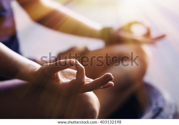 Cierre de las manos de la mujer meditando en interiores
