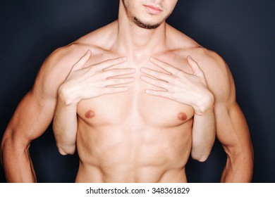 Closeup of woman's hands on muscular man's chest
