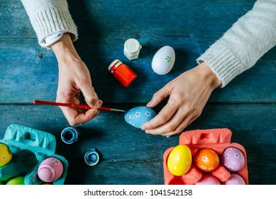 Close-up of woman's hands painting an easter egg.