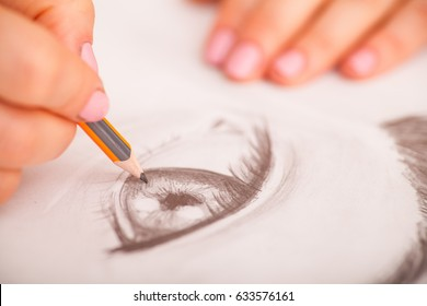 Closeup of woman's hands with a pencil drawing human eye at the desk