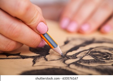 Closeup of woman's hands with a pencil drawing beautiful bunch of roses at the desk