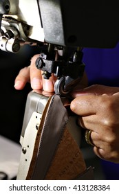 Closeup of a woman's hands as she operates an industrial sewing machine in a shoe factory, hand-stitching a the leather upper of a shoe. Shallow depth of field.