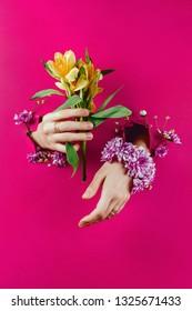 Closeup of woman's hands through torn paper holding yellow alstroemerias and chrysanthemum bracelet, selective focus