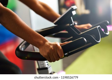 Close-up of woman's hands training at a gym doing cyclo indoor. Sports and fitness concept.