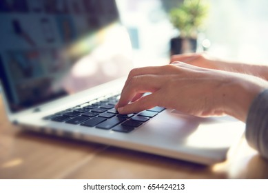 Closeup woman's hands typing on a laptop on a wooden desk with sunlight.
