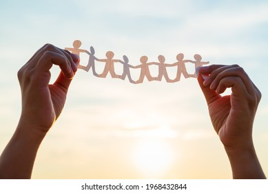 Closeup woman's hands unfold the paper human chain over the sunset sky to see the result after finish cutting, teamwork concept