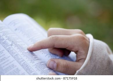 Nahaufnahme von Frauenhänden beim Lesen der Bibel draußen.