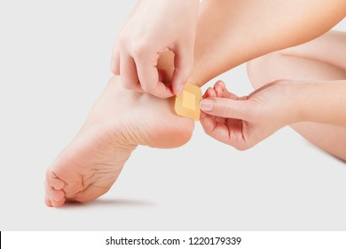 Closeup of woman's heel with blister plaster on. Patch on the blister on the leg. First aid