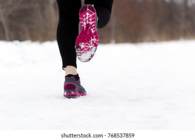 Close-up of woman's jogging shoes on nature trail on cold winter day.  Fitness and wellness lifestyle concept.