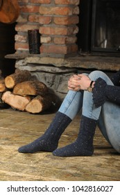 Close-up of a woman's knitted stockings near a fireplace