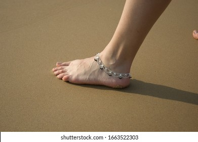 Closeup of a woman's legs with an anklet jewelry on the beach
