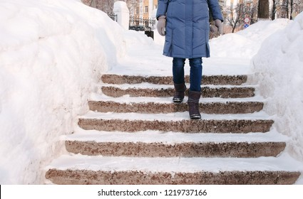Closeup woman's legs goes down on a snowy ladder, staircase. Winter park in the city during the day in snowy weather with falling snow.