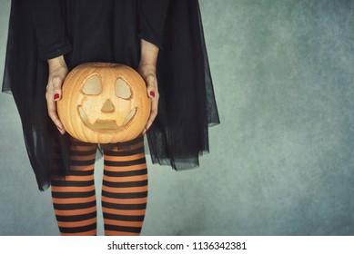 Close-up woman's legs with halloween pumpkin
