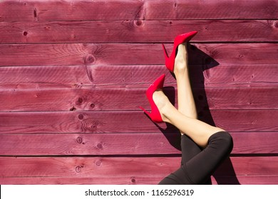 Closeup of woman's legs wearing red high heels.