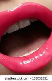 Close-up of woman's lips with bright fashion pink lipstick makeup. Macro magenta lipgloss make-up
