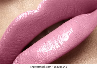 Close-up of woman's lips with bright fashion pink glossy makeup. Macro magenta lipgloss make-up