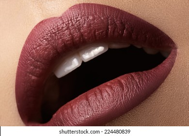 Close-up of woman's lips with bright fashion dark red makeup. Macro cherry lips make-up. Evening sexy visage