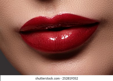 Close-up of woman's lips with bright fashion red glossy makeup. Macro cherry color lipgloss make-up. Sexy kiss