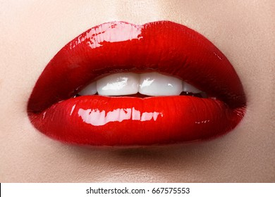 Close-up of woman's lips with bright fashion red glossy makeup. Macro bloody lipgloss make-up