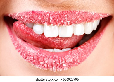 Closeup of woman's lips covered with sugar. Toothy smile