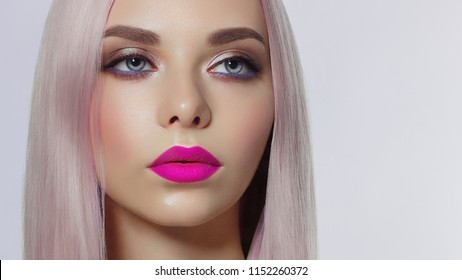 Close-up of woman's lips with fashion bright pink make-up. Beautiful female mouth, full lips with perfect makeup. Part of female face. Choice lipstick. Pink wavy hair of a Barbie doll