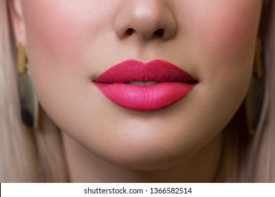 Close-up of woman's lips with fashion bright pink make-up. Beautiful female mouth, full lips with perfect makeup. Part of female face. Choice lipstick. Pink wavy hair of a doll