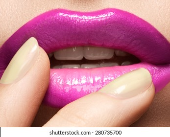 Close-up of woman's lips with fashion hot pink lipstick makeup. Beauty macro sexy make-up with naturel beige manicure.