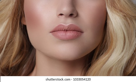 Close-up of woman's lips with fashion natural beige lipstick makeup. Macro sexy pale lipgloss make-up . Gentle pure skin and wavy blonde hair. Cosmetology, Spa, increase in lips