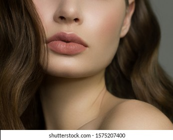 Close-up of woman's lips with fashion natural beige lipstick makeup. Macro sexy pale lipgloss make-up . Gentle pure skin and wavy brunet hair. Cosmetology, Spa, increase in lips