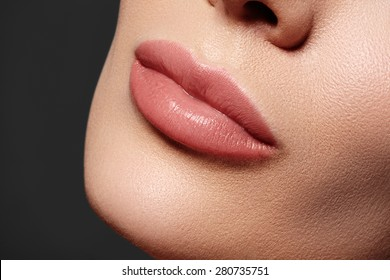 Close-up of woman's lips with fashion natural beige lipstick makeup. Horizontal macro sexy pale lipgloss make-up