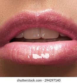 Close-up of woman's lips with fashion natural rose lipstick makeup. Horizontal macro sexy pale lipgloss make-up