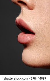 Close-up of woman's lips with fashion natural beige lipstick makeup. Side view macro sexy pale lip make-up