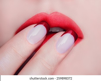 Close-up of  woman's lips with natural light makeup. Beauty macro sexy female mouth and french manicure on nails.