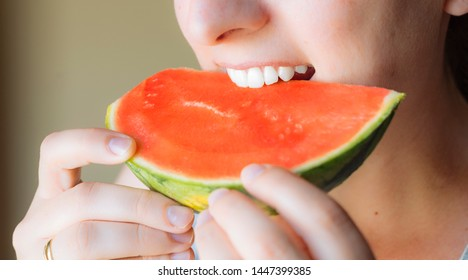 Close-up of a woman's mouth biting a slice of watermelon. healthy lifestyle. White teeth Perfect denture after using brackets.
