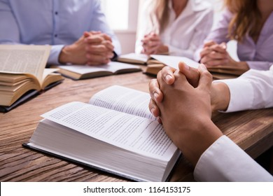 Close-up Of A Woman's Praying Hand On Bible Over Wooden Desk