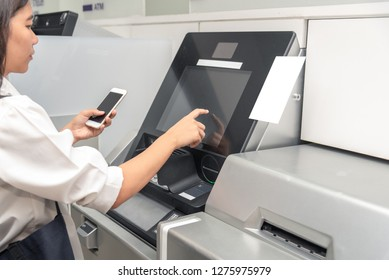 Closeup of women business hands using smart phone while typing on ATM, bank machine