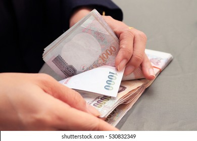 Closeup women hand counting Thai money banknote one thousand thai baht. Business and financial concept isolated in white background.