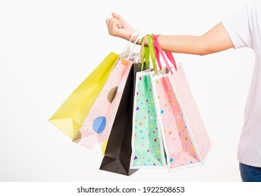 Closeup women hand holding colorful multicolor shopping bag many packets isolated on white background, female holds in hand white clear empty blank craft paper gift bag, shopping day concept
