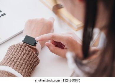Closeup of women hand using his smartwatch touchscreen standing on the table.