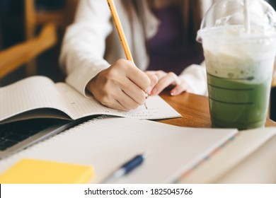 Closeup women hand writing note for math study and work online at cafe. University people activity campus lifestyle on day time concept.