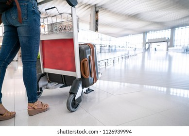 Close-up women is pushing the trolley with suitcases at the airport.