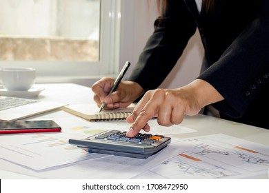 Close-up of women using calculators to create accounting reports by the window in their own homes, cost calculation concepts, and work at home concepts.